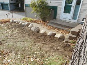 Create drainage swale using boulders